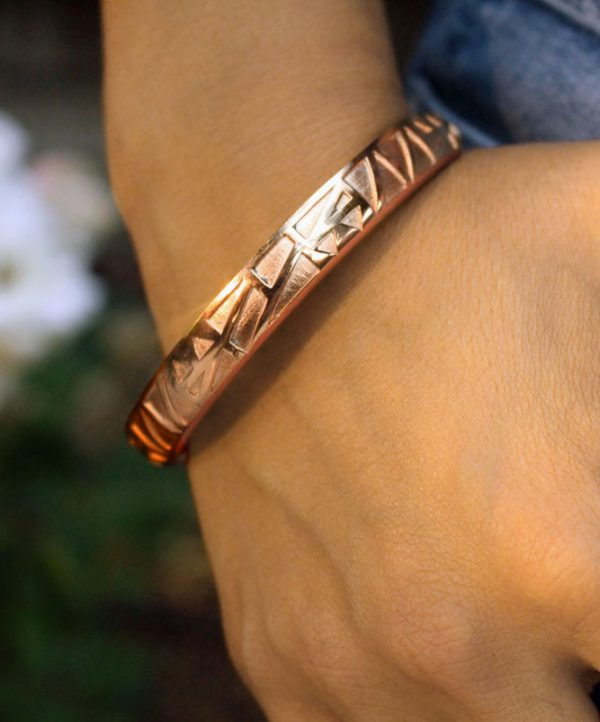Bangle & Band rose gold hair tie bracelet; this beautiful piece of jewelry features a narrow channel on the side of the bangle for the purpose of holding a hair tie.